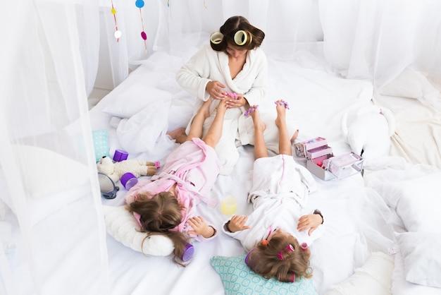 Vrouw en kinderen op bed