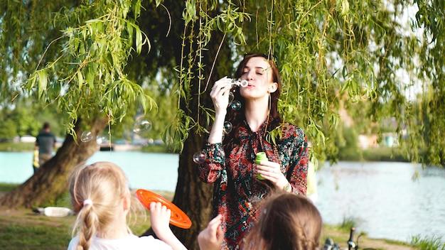 Vrouw en kinderen spelen met zeepballonnen. romantisch portret van jonge vrouw met zeepballonnen. sunny valley op een zomerse dag