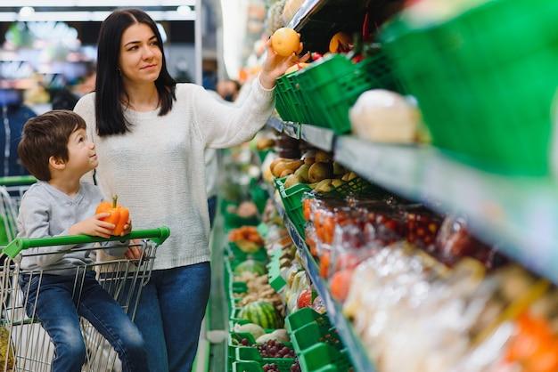 Vrouw en kindjongen tijdens familie winkelen met karretje bij supermarkt