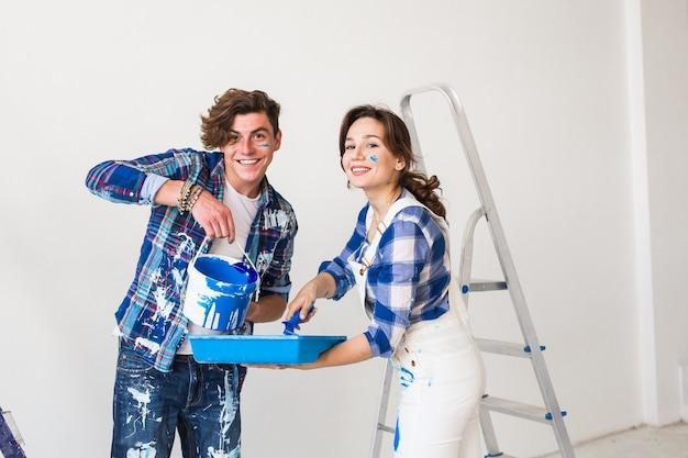 Vrouw en knappe man schildert de muur in nieuw appartement.