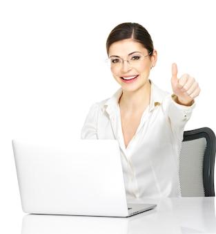Vrouw en laptop met duimen ondertekenen omhoog in wit bureauoverhemd - dat op witte achtergrond wordt geïsoleerd.