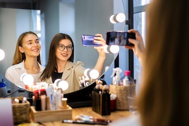 Vrouw en make-upkunstenaar die een selfie nemen