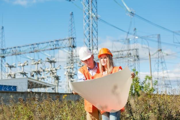 Vrouw en man aan het werk als architecten op een bouwplaats