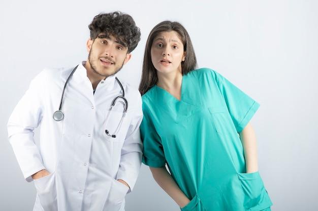 Vrouw en man artsen staan en kijken verrassend naar de camera.
