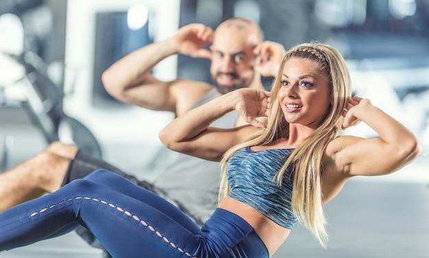 Vrouw en man atletisch paar versterken buikspieren in sportschool. core krachttraining oefening.