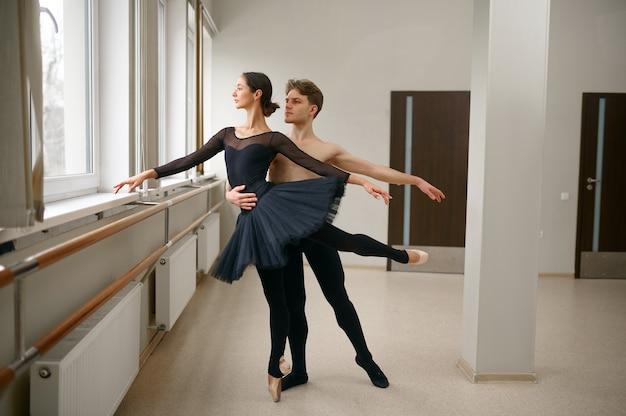 Vrouw en man balletdansers dansen op barre