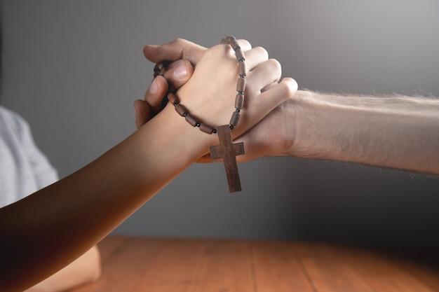 Vrouw en man bidden met een kruis vast