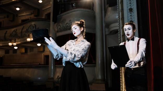 Vrouw en man bootst kunstenaar repeteren op het podium in het auditorium na