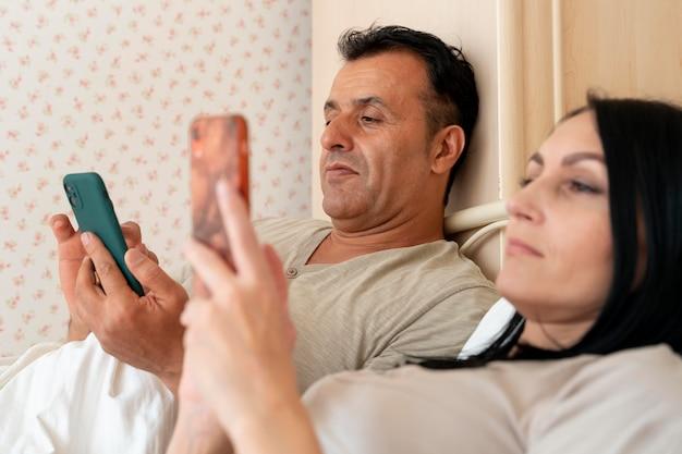 Vrouw en man controleren hun telefoon in bed