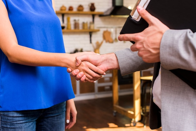 Vrouw en man die een overeenkomstclose-up bereiken