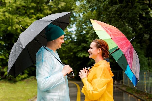 Vrouw en man die elkaar bekijken terwijl het houden van hun paraplu's