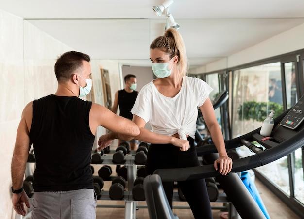 Vrouw en man die elleboog gebruiken om elkaar te groeten in de sportschool