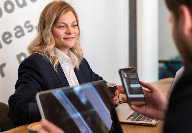 Vrouw en man die hun telefoon controleren tijdens een vergadering