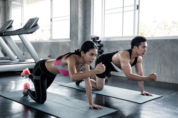 Vrouw en man die op yogamat uitoefenen.