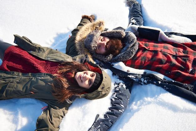 Vrouw en man die sneeuwengel maken