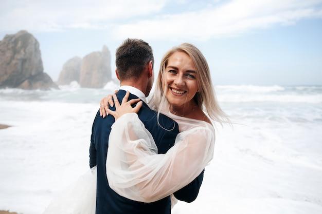 Vrouw en man die tribune op het oceaanstrand koesteren