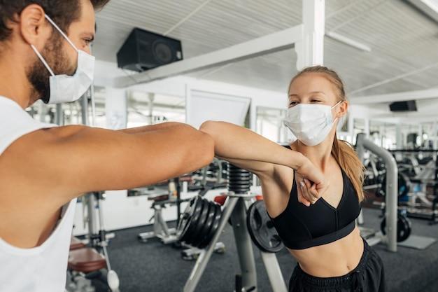 Vrouw en man doen de ellebooggroet in de sportschool
