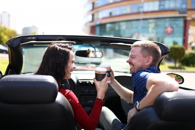 Vrouw en man drinken een warme drank in de auto en lachen. positief communicatie- en tijdverdrijfconcept