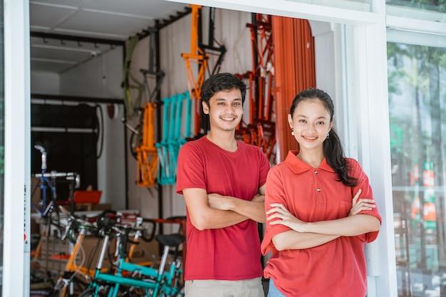 Vrouw en man fietsenwinkel eigenaar met gevouwen armen staan voor de winkel
