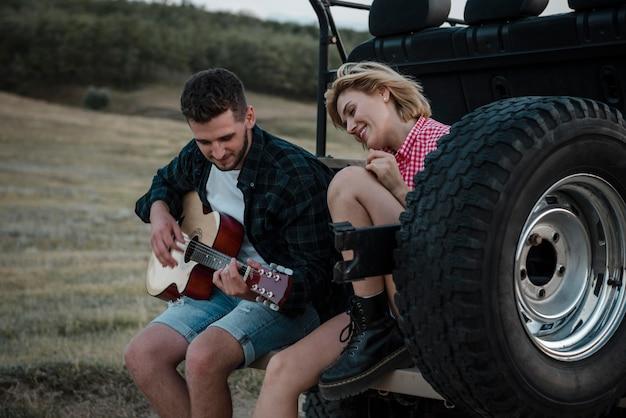 Vrouw en man gitaarspelen tijdens het reizen met de auto