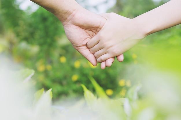 Vrouw en man hand in hand, gelukkige paar liefde in de tuin.