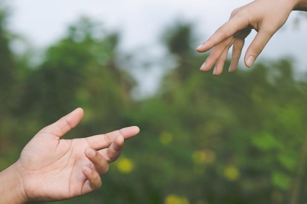 Vrouw en man hand in hand, gelukkige paar minnaar in het park.