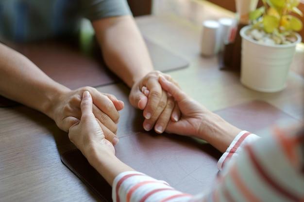 Vrouw en man hand in hand nemen samen zorg