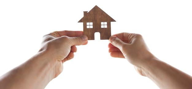 Vrouw en man houden het houten huisje in hun handen