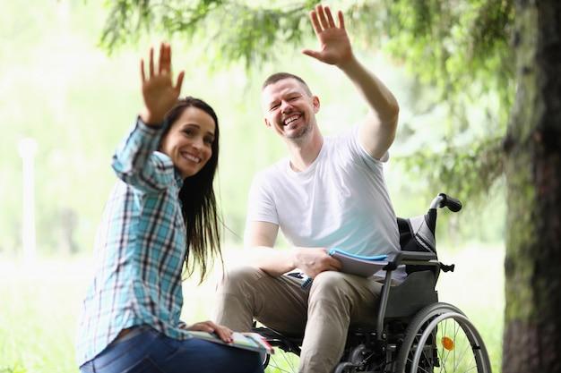 Vrouw en man in rolstoel zwaaien gelukkig