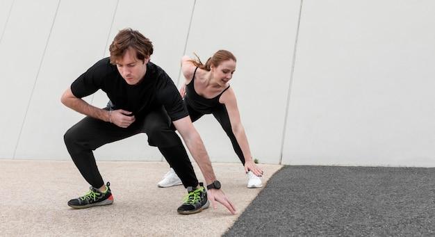 Vrouw en man in sportkleding buiten oefenen