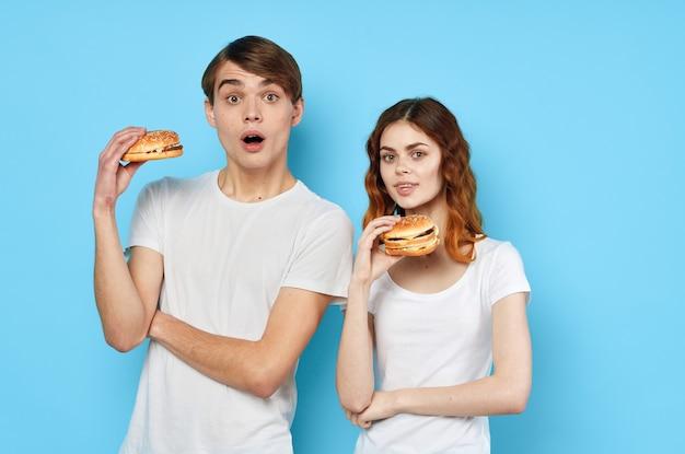 Vrouw en man in witte t-shirts fastfood dieet blauwe achtergrond