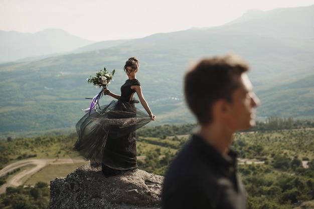Vrouw en man in zwarte kleding buitenshuis. zwarte trouwjurk.