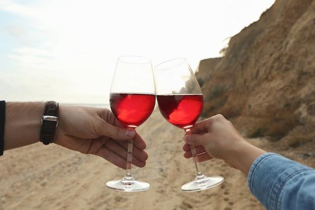 Vrouw en man juichen met wijn op zandstrand