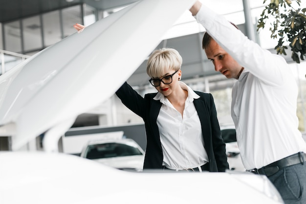 Vrouw en man kiezen een auto in de dealer en kijken onder de motorkap van een auto