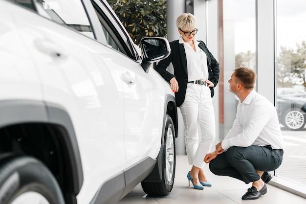 Vrouw en man kiezen een auto in de dealer. vrouw leunde op de auto en man zit ernaast