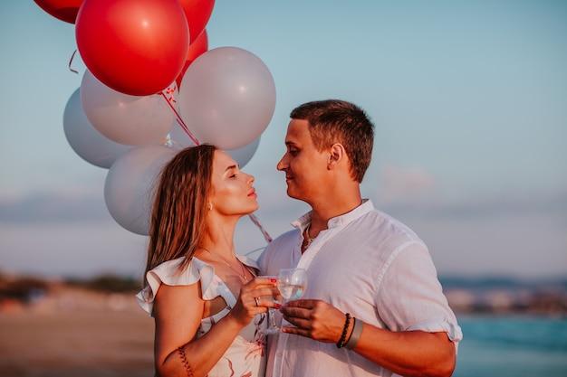 Vrouw en man knuffelen en vieren samen met champagne en ballonnen aan de kust.