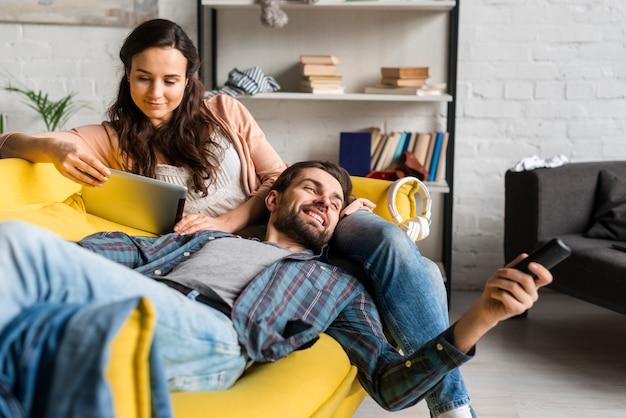 Vrouw en man lezen en gebruiken van de afstandsbediening