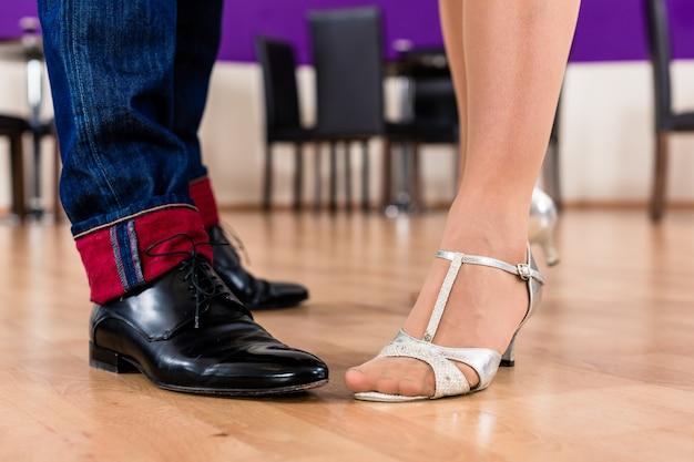 Vrouw en man met haar dansschoenen in dansschool