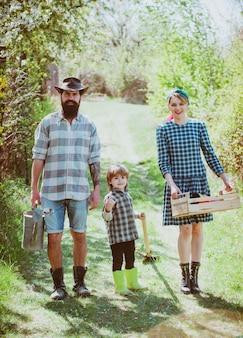 Vrouw en man met zoon planten in de moestuin worden biologische boeren een paar met kind ...