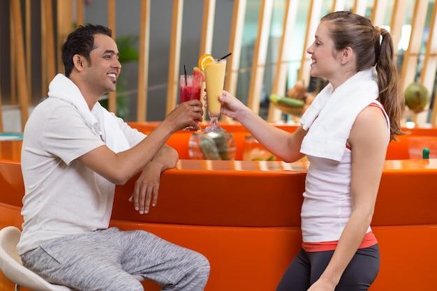 Vrouw en man roosteren met vruchtensappen in een bar