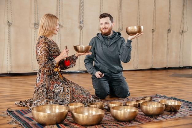 Vrouw en man spelen op een tibetaanse klankschaal voor zitten met geluidstherapie