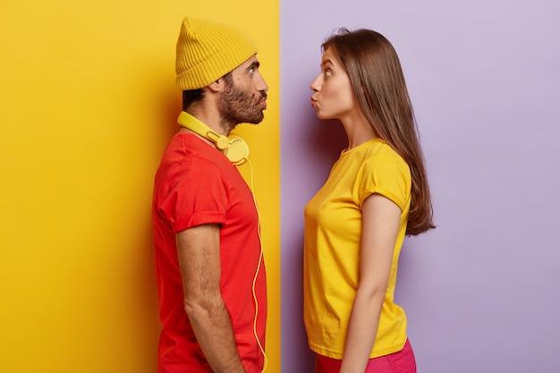Vrouw en man staan in profiel, houden de lippen gevouwen, staren elkaar aan, gaan elkaar kussen, dragen casual t-shirts, koptelefoons om de nek, grimassen maken, poseren indoor, veel plezier. gezichtsuitdrukkingen concept