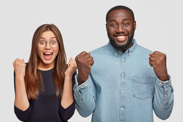 Vrouw en man van gemengd ras zegevieren en voelen geluk na het winnen van de eerste plaats