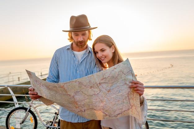 Vrouw en man verliefd reizen op de fiets bij zonsondergang op zee