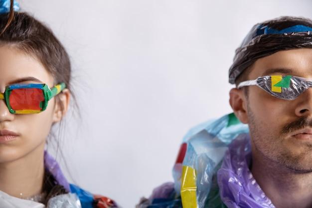 Vrouw en man verslaafd aan verkoop en kleding die plastic recyclingconcept dragen