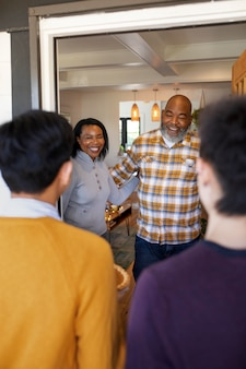 Vrouw en man verwelkomen familieleden voor het thanksgiving-diner