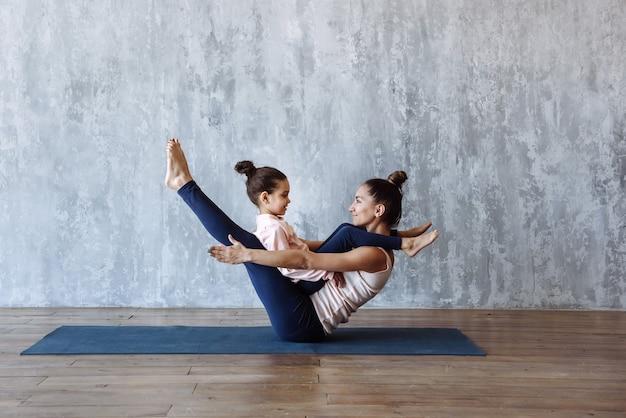 Vrouw en meisje beoefenen samen yoga op de vloer