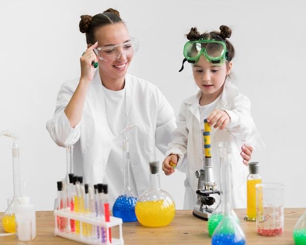 Vrouw en meisje die wetenschapsbuizen gebruiken