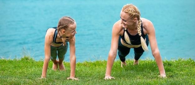 Vrouw en meisje doen push-up oefening op het gras in de buurt van meer buitenshuis