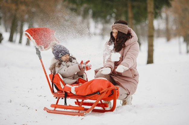Vrouw en meisje in een park met slee